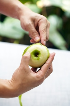 リンゴの皮をむくナイフを使用して手