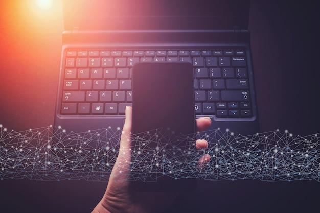Рука с помощью ноутбука и мобильного телефона на столе в офисе с цифровой сетевой линией. творческий фон подключения, сеть нового поколения имеет ограничение скорости беспроводной связи, смешанную среду.