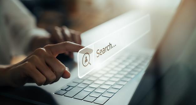 ラップトップを使用して手で画面を押して、インターネット上のブラウジングをオンラインで検索します。