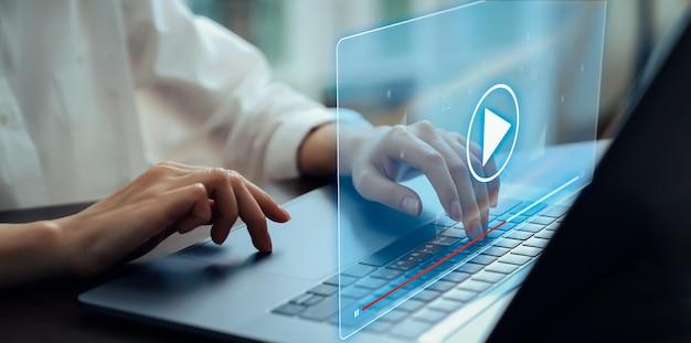노트북을 사용하여 손을 잡고 인터넷에서 온라인으로 비디오 스트리밍 화면을 누르십시오. 개념 통신 네트워크.