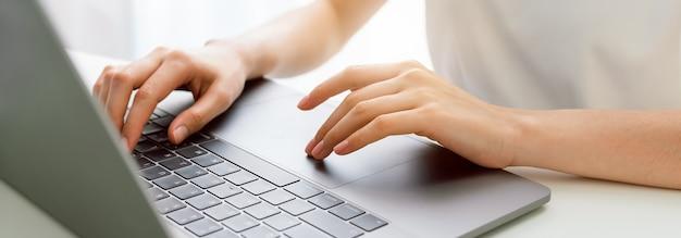 Рука с помощью ноутбука в офисе.