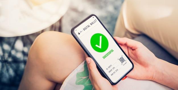 성공적인 결제 화면을 위해 휴대 전화를 사용하는 손. 스마트 폰에서 쇼핑하고 온라인으로 애플리케이션 지갑에서 뱅킹을합니다.