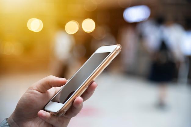 都市の光の背景がぼやけている携帯電話を使用して手。現代の無線技術。ネットワーク