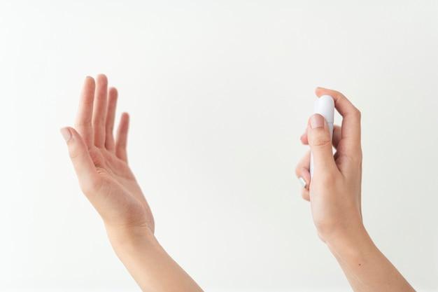 Mano utilizzando un disinfettante per le mani portatile