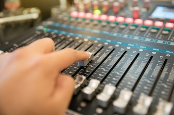 Hand using professional audio mixing console to control the sound