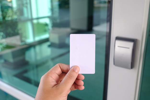 Hand using security key card scanning to open the door to entering office building or home or bank