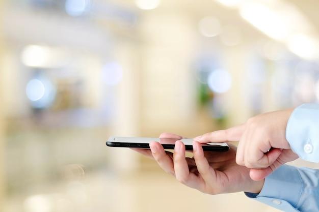 Hand using smart phone over blur bokeh light background