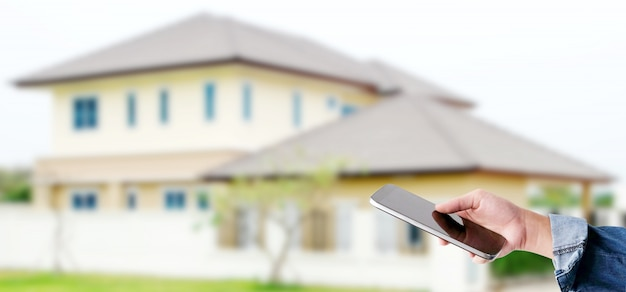 Hand using smart phone over blur house, smart home control concept