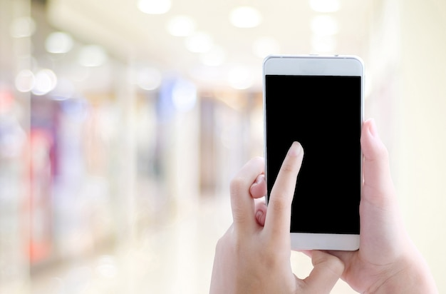 空の上に空白の画面を持つスマートフォンを使用して手ぼかしの光の背景