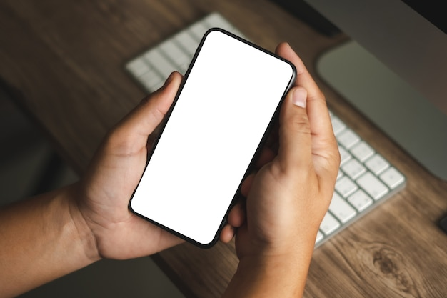 Hand using a smartphone man holding cell phone with blank screen