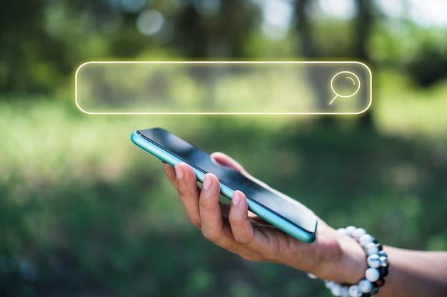 Рука с помощью смартфона ищет информацию в интернете со значком окна поиска. copyspace.