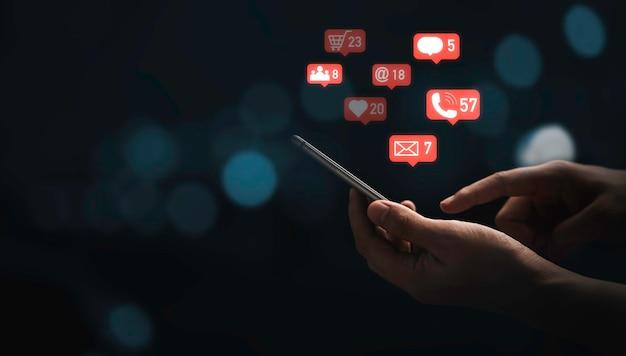 スマートフォンを使用して、マーケティング情報の概念のための青いボケ味の背景を持つメッセージとソーシャルメディアのアイコンを送信する手。