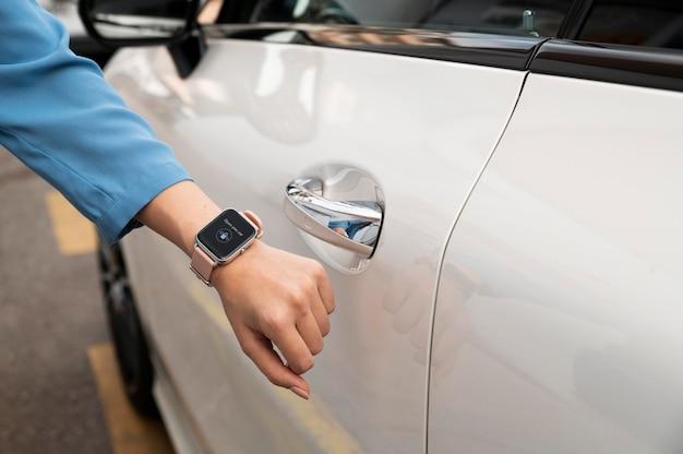 손으로 스마트 워치를 사용하여 자동차 잠금 해제 클로즈업