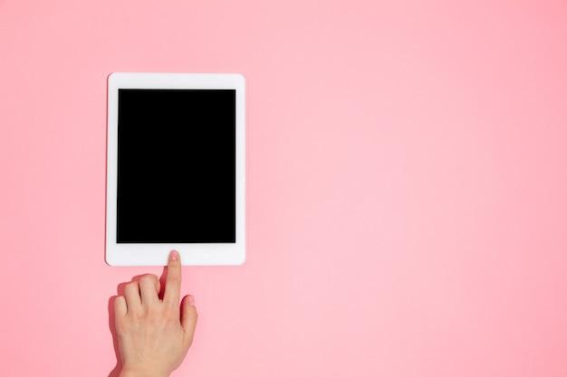 Рука с помощью планшета, устройство на виде сверху, пустой экран с copyspace, минималистичный стиль. технологии, модерн, маркетинг. . коралловый цвет на стене. стильно, модно.