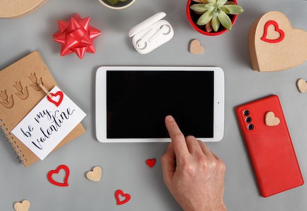 ギフトボックスの近くでタブレットを使用して手で灰色のテーブルに私のバレンタインカードの上面図