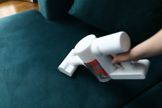 Hand vacuums upholstered furniture in apartment