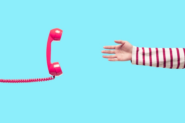 Hand and vintage pink telephone