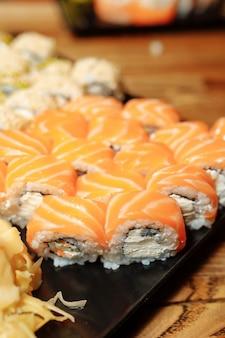 セットを持っているハンドウェイター伝統的なレストランでおいしい新鮮な寿司スレートプレート、日本の生の魚。フィラデルフィアの生春巻きを寿司バーの皿に盛り付けました。手袋をはめたウェイターが巻き寿司を持っています。