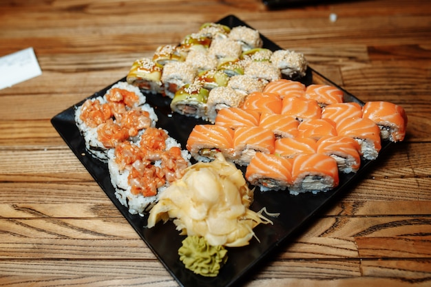 Hand waiter holding set delicious fresh sushi slate plate japanese raw fish in traditional