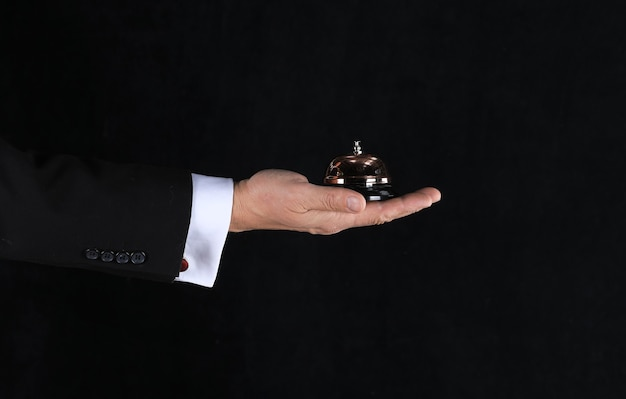 Hand of a waiter with a service call on a black background