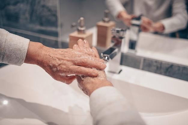 手洗い泡液体石鹸こすり手首手洗いステップ年配の女性がバスルームの蛇口シンクで水ですすぎます。 covid-19の広がりを防ぐために手を洗ってください。コロナウイルスの大流行。