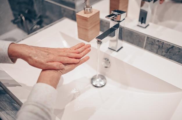 Ручная стирка пены жидкое мыло втирание запястий руки мытье шаг старшая женщина полоскание в воде в ванной кран раковина.