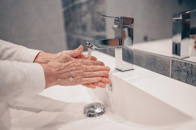 手洗い泡液体石鹸こすり手首手洗いステップ年配の女性がバスルームの蛇口シンクで水ですすぎます。