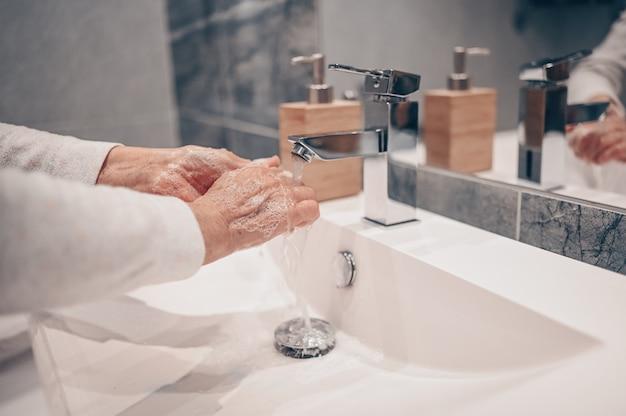 Hand washing lather liquid soap rubbing wrists handwash step senior woman rinsing in water at bathroom faucet sink