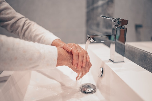 Hand washing lather liquid soap rubbing wrists handwash step senior woman rinsing in water at bathroom faucet sink.