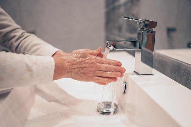 Hand washing lather liquid soap rubbing wrists handwash step senior woman rinsing in water at bathroom faucet sink.