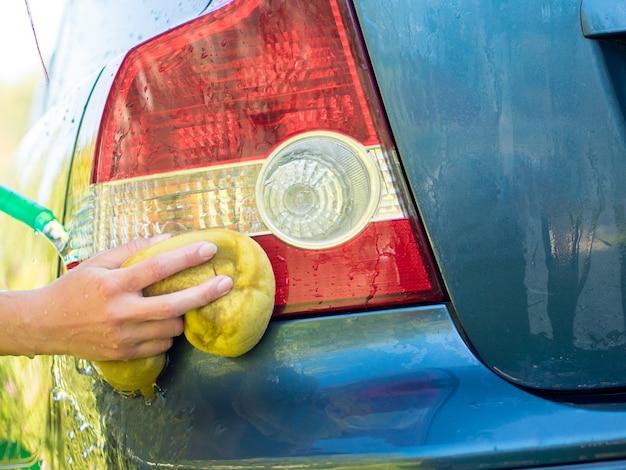 Hand washing rear lights of blue car by sponge