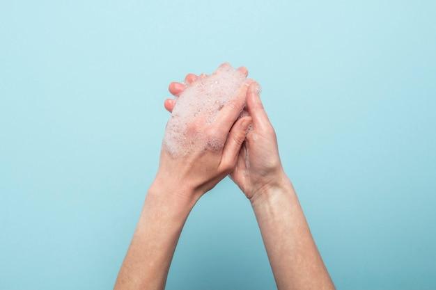 手洗い。青に石鹸の女性の手