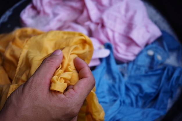 Hand washing yellow, pink, blue shirt with bubble white basin.