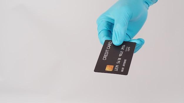 흰색 바탕에 검은색 신용 카드를 들고 있는 파란색 의료용 장갑을 손에 끼세요.