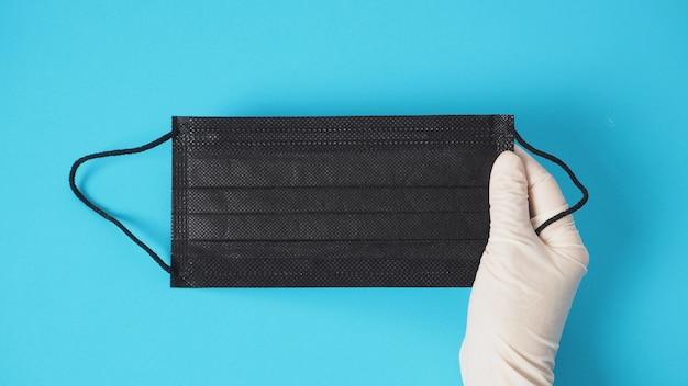 ハンドウェアの白い手袋は、ウイルス感染や化学物質から保護するために黒いフェイスマスクを保持しています。青い背景を置きます。