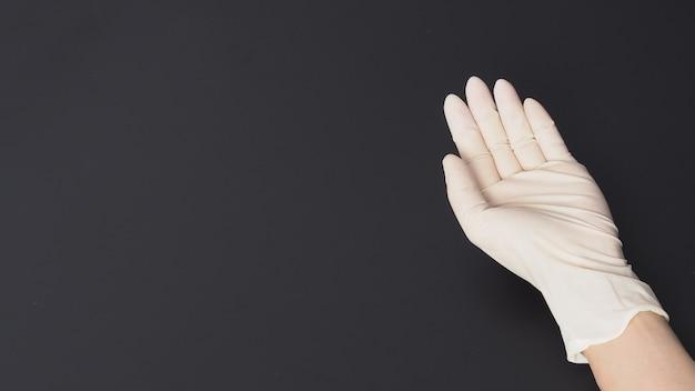 手は白いラテックス手袋を着用し、黒い背景に手をつないでください。