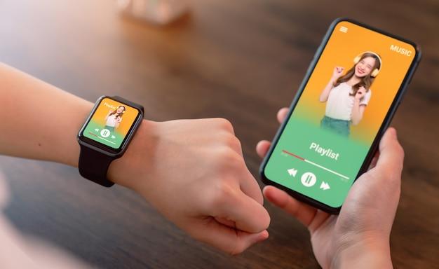 손으로 착용할 수 있는 스마트워치와 쇼 응용 프로그램 음악 즐겨찾기 재생 목록 화면이 있는 스마트폰을 들고 있습니다.