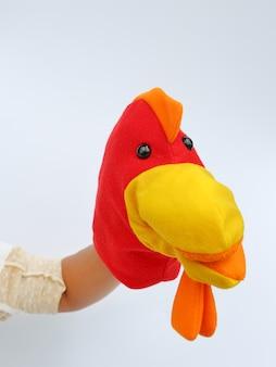 Hand wearing children puppets, chicken head
