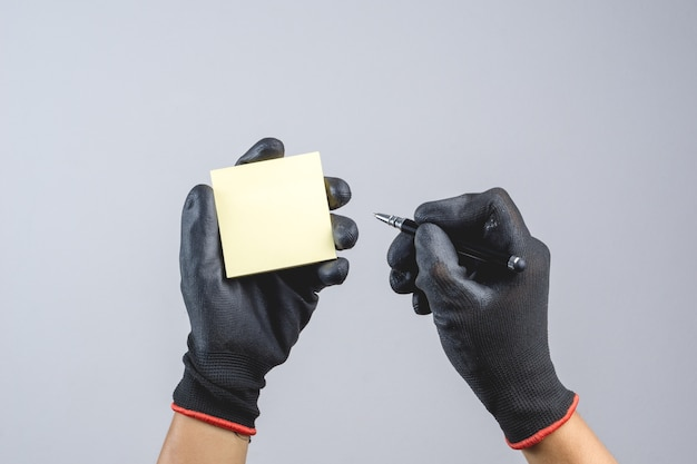 Hand wearing dark glove and holding pen and sticky paper note