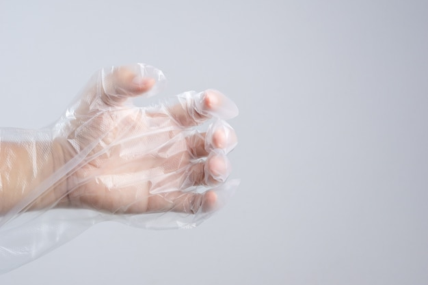 Hand wearing disposable protective plastic glove holding something like a bottle