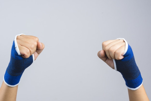 Hand wearing elastic hand and wrist support with clenched fist as fighting gesture