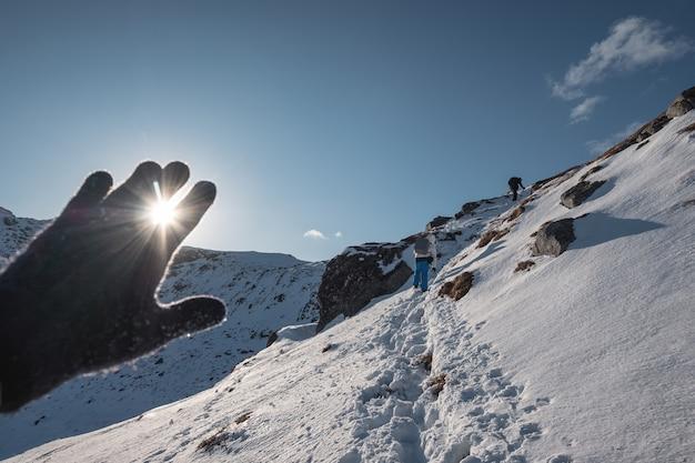 Рука в перчатке, покрывающей солнечные звезды на вершине горы