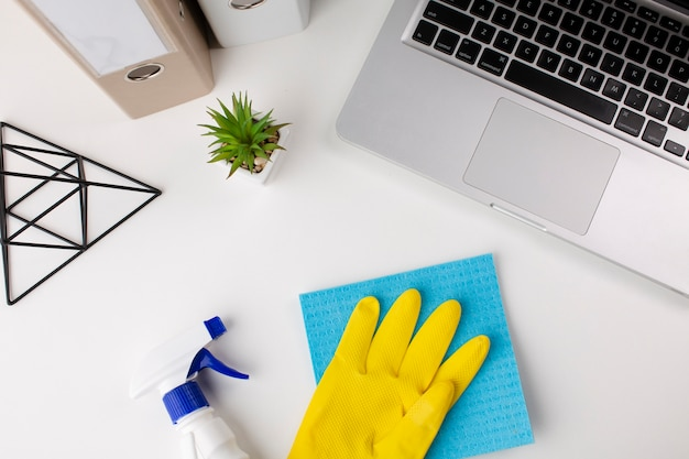 Hand wearing gloves cleaning desk