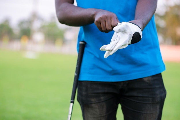 Hand wearing golf glove on tee with club in golf course