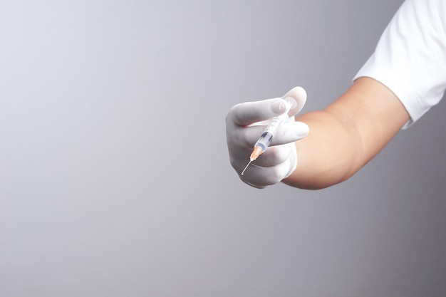 Hand wearing latex glove holding syringe with a medicine