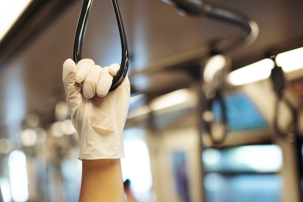 Hand wearing a latex glove while holding a train handrail  to prevent coronavirus contamination