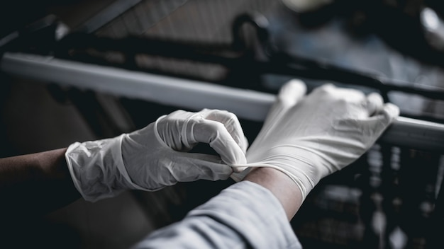 Hand wearing a latex glove while pushing a shopping cart to prevent coronavirus contamination