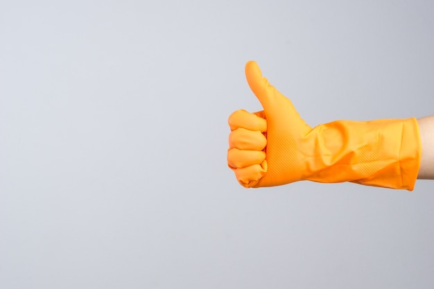 Hand wearing protective rubber glove with thumb up gesture