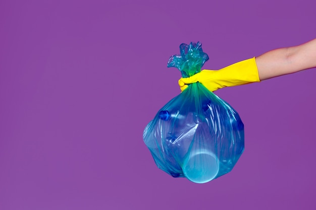 A hand wearing a rubber glove holds transparent garbage bag