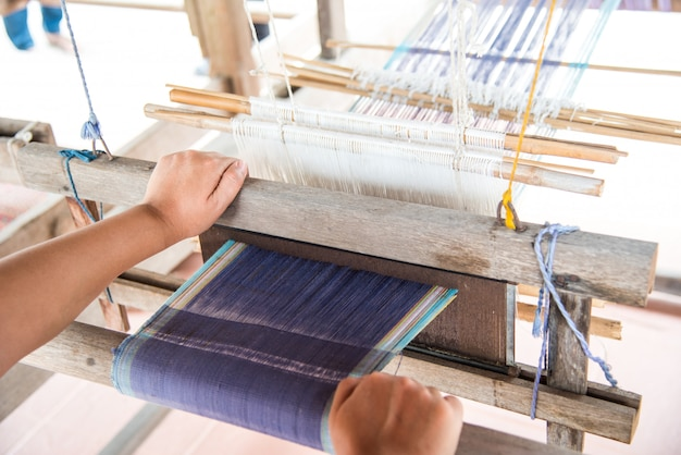 The hand of a weaver is woven with a hand-woven machine